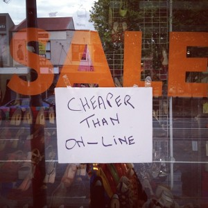 cheaper than on-line sign in shop window